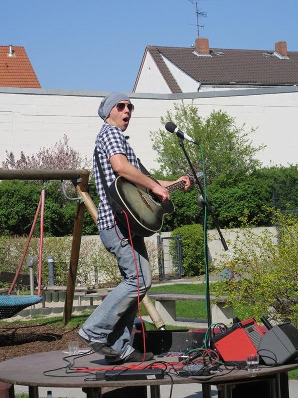 Julian Thoma spiel mit Gitarre im Hof des AWO Seniorenzentrums in Worms
