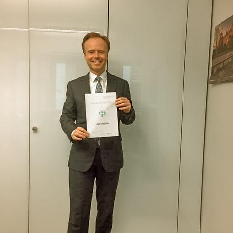 Politiker Jan Metzler hält Urkunde für sein Ehrenamt in der Hand