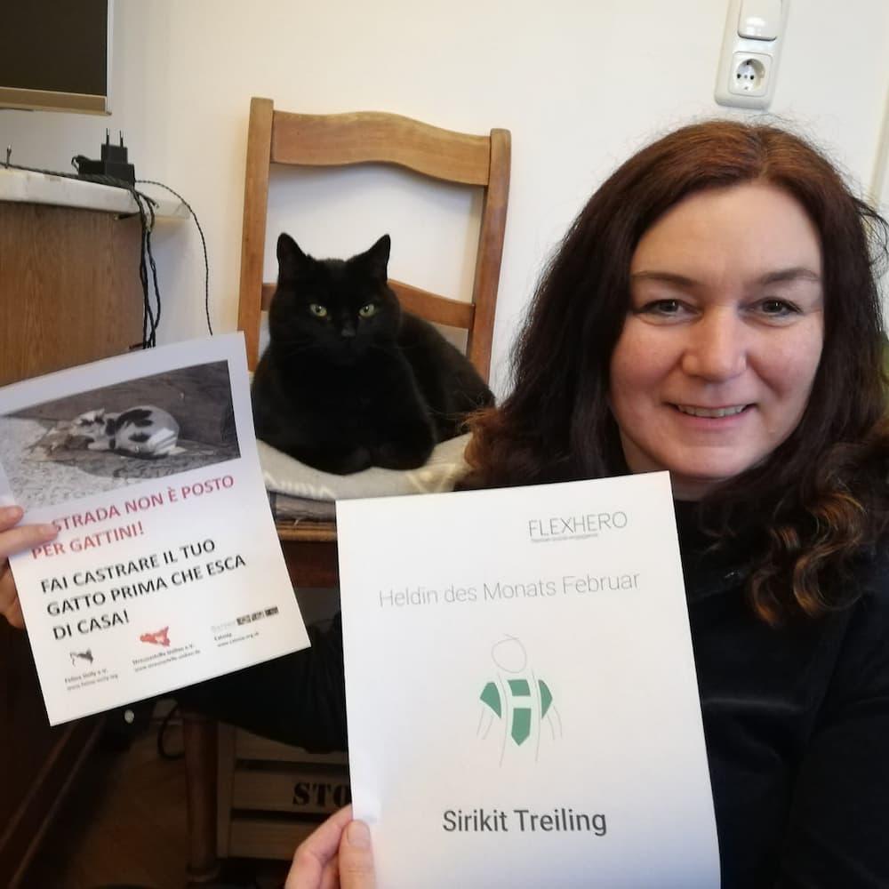 Heldin im Ehrenamt hält Urkunde in der Hand. Im Hintergrund eine Katze