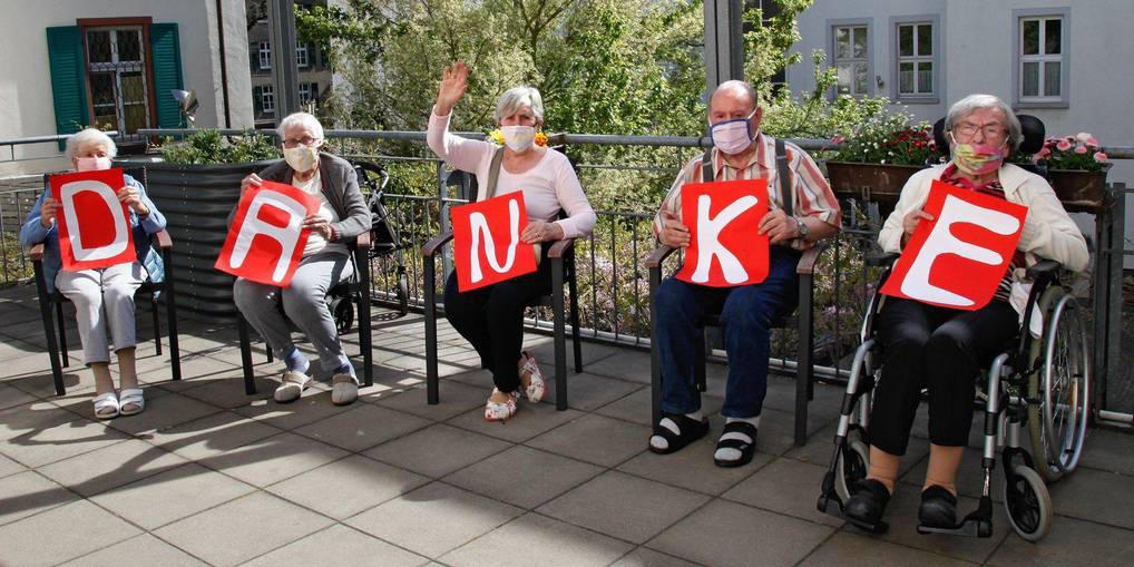 Senioren des Seniorenzentrum halten Danke-Schilder in den Händen. Sie sagen Danke für die genähten Masken