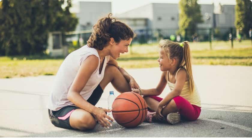 Frau sitzt mit Kind nach Ballspiel auf Boden