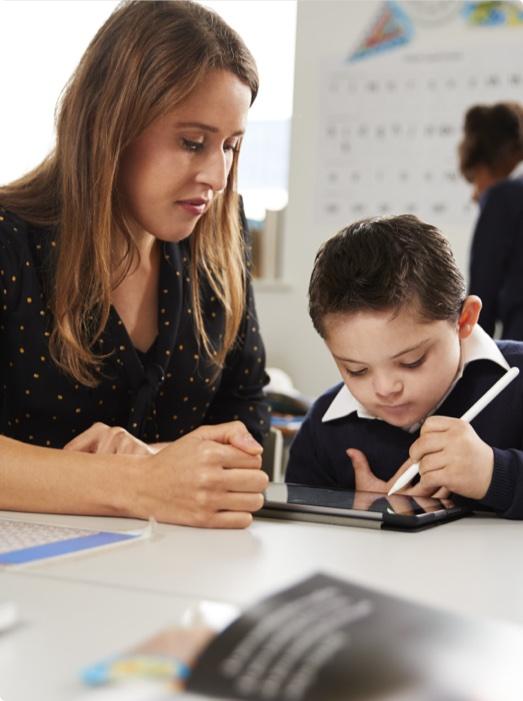 Junge Frau hilft kleinem Jungen bei den Hausaufgaben. Sie arbeiten mit Tablet im Rahmen der Digitalisierung im Ehrenamt