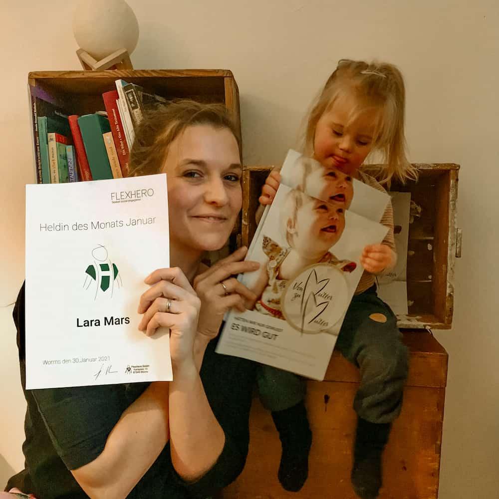 Heldin des Monats Januar 2021 Lara Mars mit Ihrer Tochter, die ein Flyer des Vereins von Mutter zu Mutter in der Hand hält