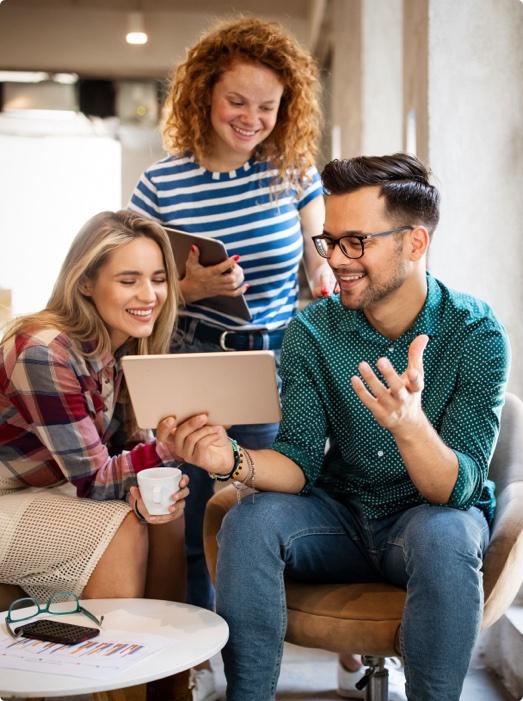 Drei Junge Menschen betrachten ein Smart Device