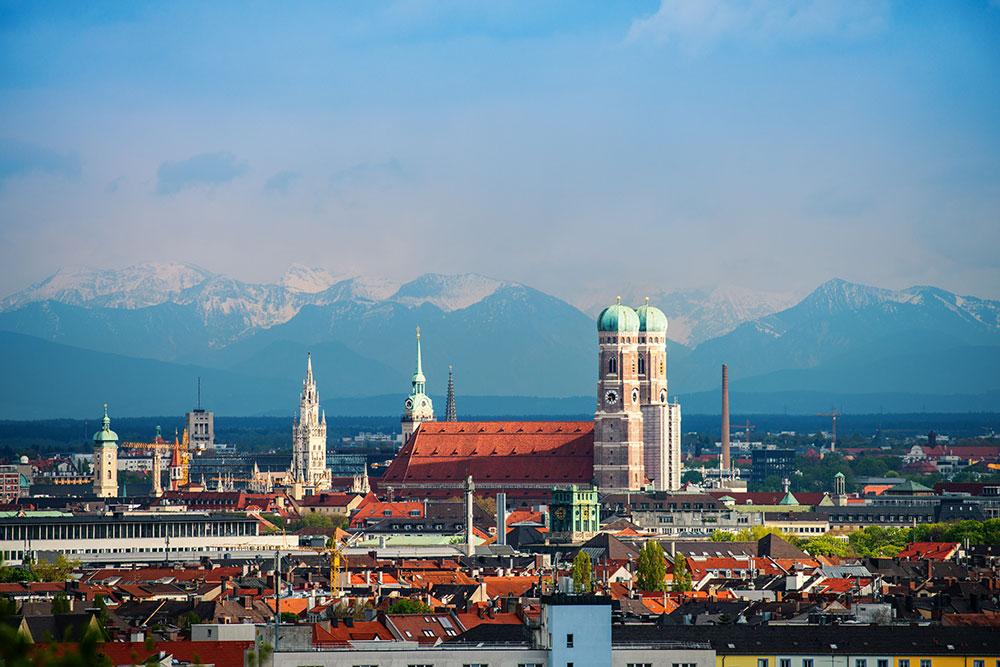 Münchner Frauentürme mit Alpen im Hintergrund als Symbolbild für das Ehrenamt in München