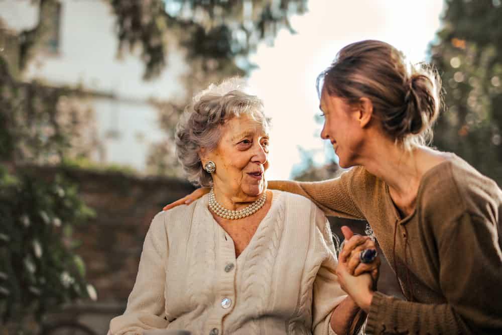Junge Frau die sich mit älterer Frau unterhält und sie stützt