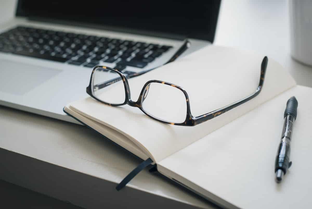 Laptop und Brille auf Notizblock als Projekt Bild für den Referenten im Ehrenamt