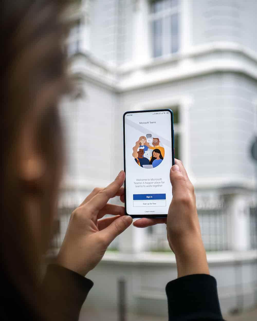 Ehrenamtliche hält Smartphone in der Hand und hält eine Videokonferenz über Microsoft Teams