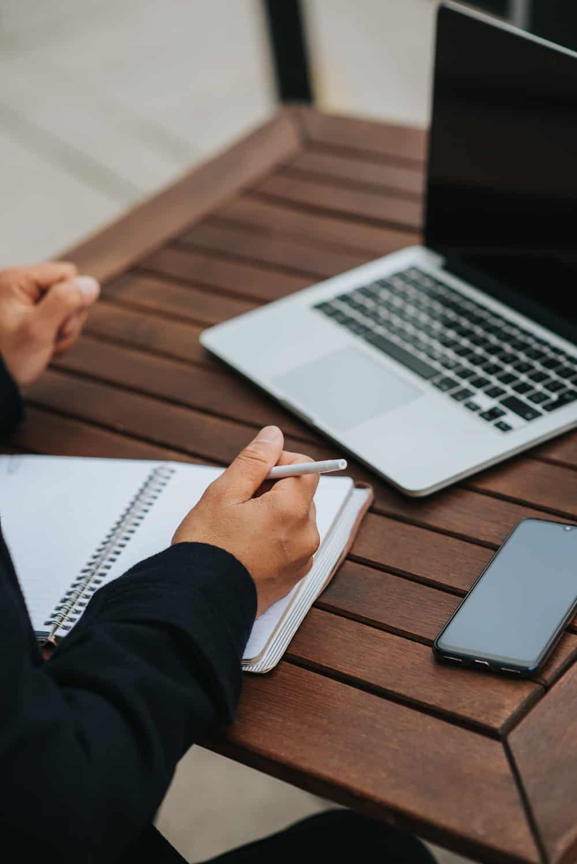 Frau macht sich Notizen während sie über ihren Laptop an einer digitalen Mitgliederversammlung teilnimmt