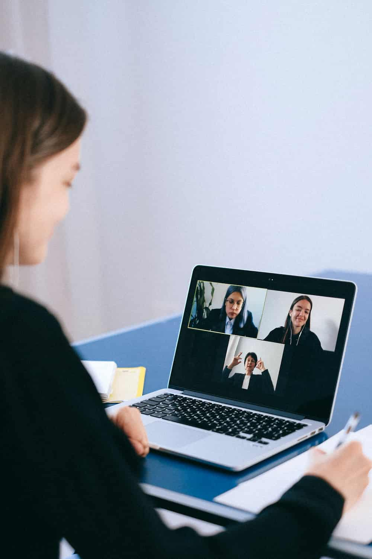 Frau vor PC in einer digitalen Mitgliederversammlung über Zoom Hochformat