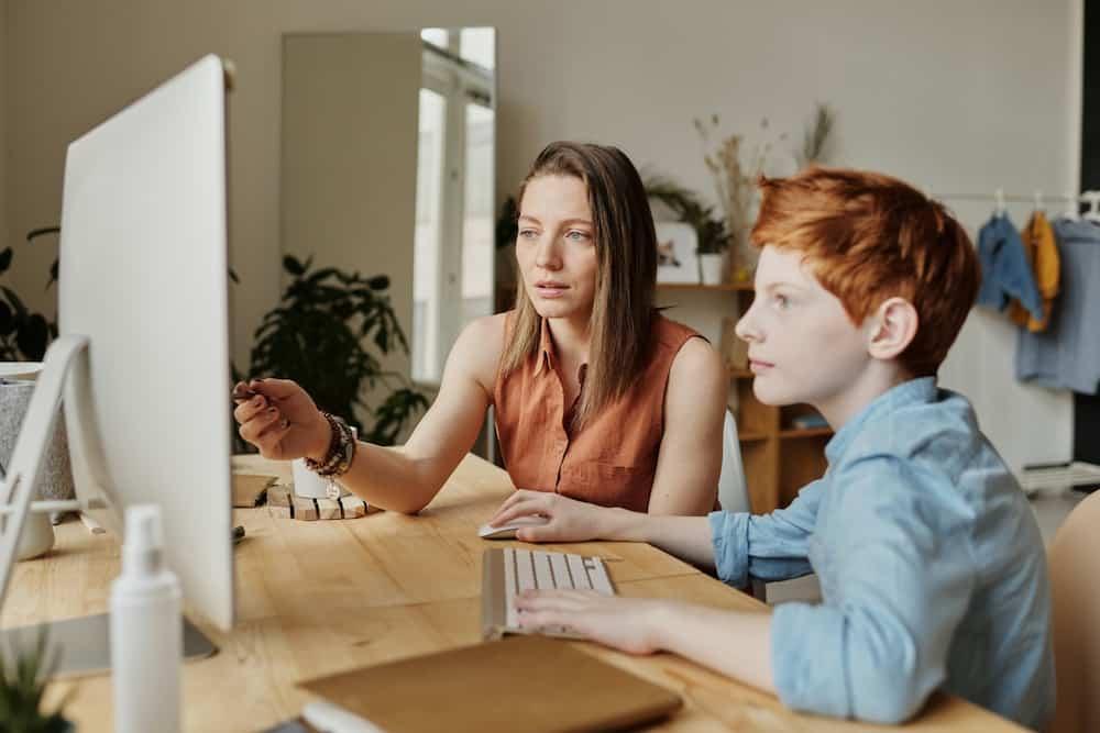 Ehrenamtliche hilft Schüler bei den Hausaufgaben