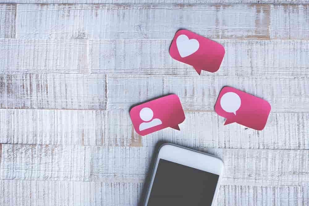 Smartphone auf Tisch mit Herz, Profil und Chat-Icon